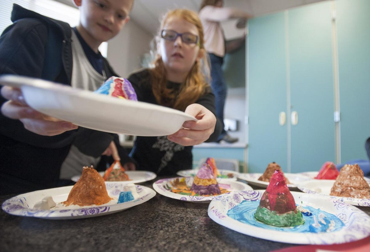 Harney Elementary School students prepare model volcanoes to erupt via a chemical reaction between baking soda and vinegar on Monday. Clark College's NERD Girls wrapped up their six-week, after-school science camp with a bang.