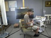 Troy Lucas, a fine arts conservator, works on a painting by an unidentified artist inside his lab.