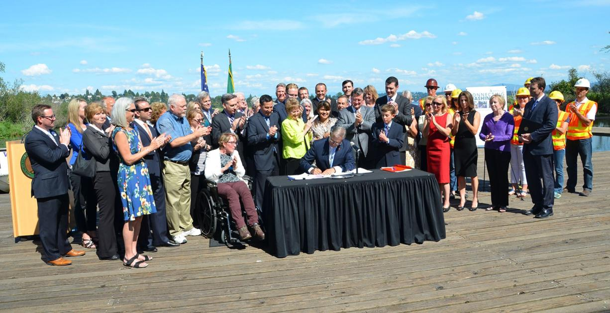"""Office of the Governor Sen. Don Benton, R-Vancouver, in blue shirt and khakis, applauds as Gov. Jay Inslee signs the transportation package into law last week. A few hours earlier, his office had announced he would attend the ceremony to voice his opposition to a """"raw deal for Clark County taxpayers and commuters."""""""