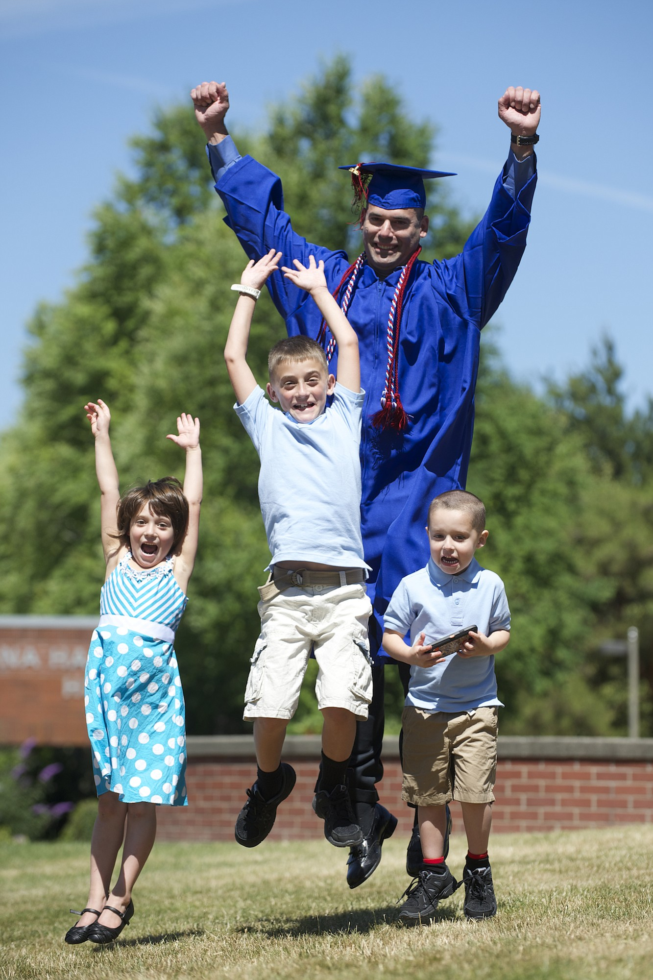 Alex Peraza, with his children, from left, Elsa Aaliyah, 6, Jacob, 8, and Preston, 4, received  his associate of arts degree at Clark College's 79th commencement Thursday night. As a boy, Peraza emigrated from Cuba with his family. He served in the U.S. military and later returned to school to be a role model for his kids.