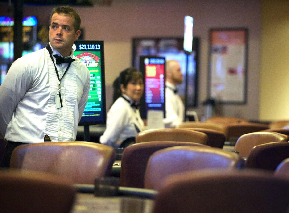 Zachary Kaufman/The Columbian Blackjack dealer Josh Skucas, 33, stands at an empty table at the Oak Tree's casino in Woodland on Tuesday. Card rooms have struggled to earn money locally, impacting the cities that collect taxes from them.