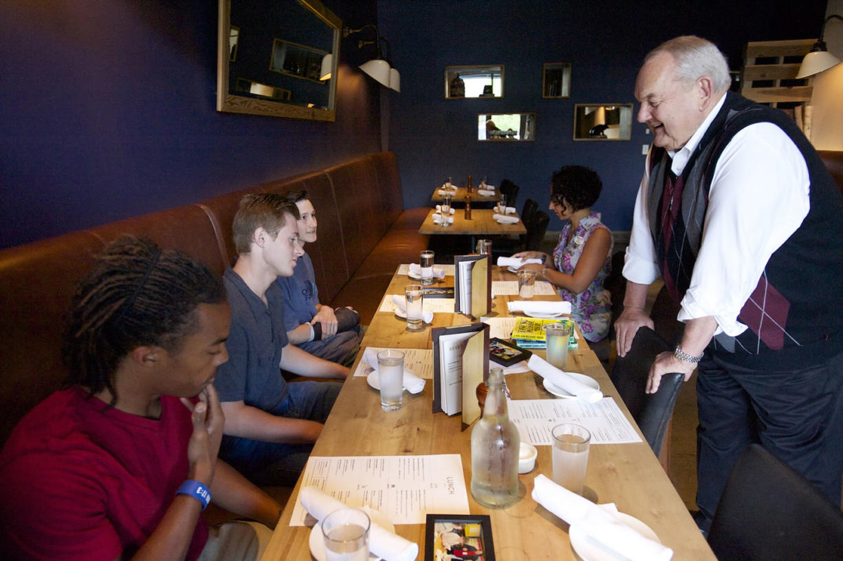 Longtime Lunch Buddy Steve Runyan greets Isaiah Ephraim, from left, Nathan Harris and Seth Hunt at Lapellah for a grown-up lunch Friday. Nine years ago Runyan began meeting with his three lunch buddies, who all attended low-income Martin Luther King Elementary.
