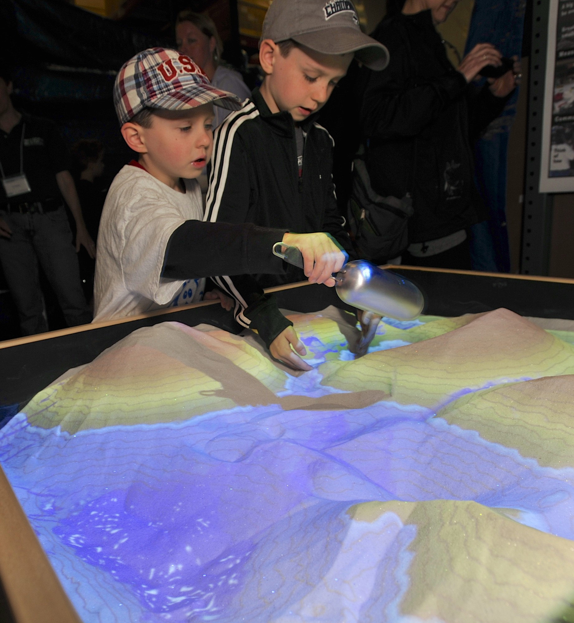 Aaron, left, and Alex Erickson play in an augmented reality sandbox, which projects topography contours on shifting sand piles, during the U.S. Geological Survey's open house at the Cascades Volcano Observatory in east Vancouver.