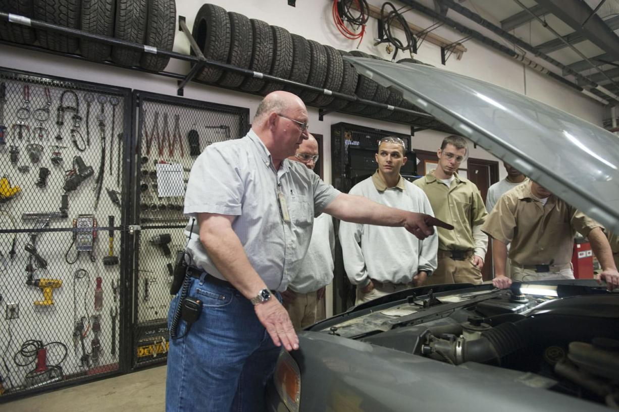Clark College instructor Bruce Music, left, teaches offenders about changing belts in an automotive repair class at Larch Corrections Center.