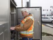 Mark Rodgers, a senior traffic signal technologist with Clark County Public Works, makes repairs at a traffic signal cabinet.
