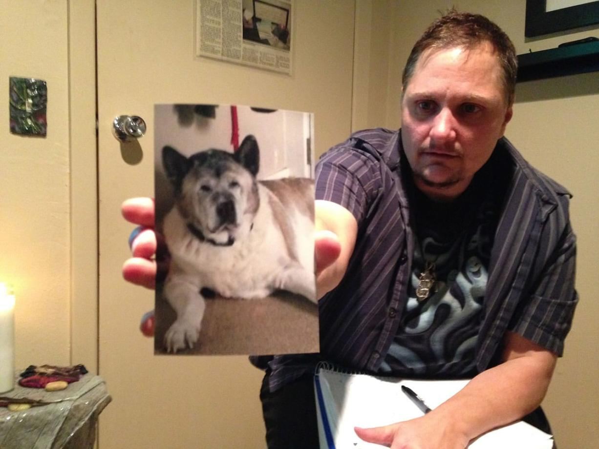Sue Vorenberg/The Columbian Psychic medium Seth Michael holds out a picture of Brittny Houghton's dog Bernie, which died recently. He said Bernie's spirit was lingering near her and still interacting with Houghton's other animals.