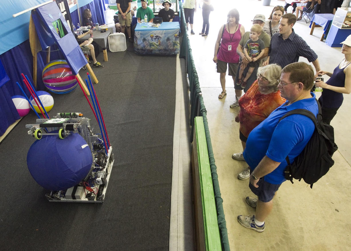 Visitors stop to watch a demonstration of a robot throwing a ball at the Clark County Fair. The 4-H high school robotics team made the robot for the annual robotics competition.