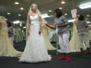 Bridal consultant Crystal Payne helps bride-to-be Cheney Ryder, 23, of Ridgefield try on wedding dresses July 23 at The Hostess House.