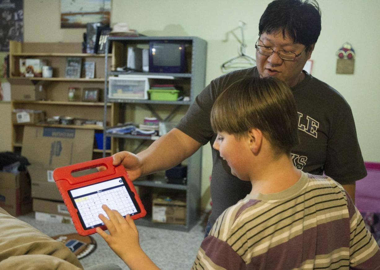 Bryce Smith holds an iPad while his son Dylan Smith, 10, tells him what activity he wants to do after dinner. Dylan is a nonverbal child on the autism spectrum. The fifth-grader attends a Structured Communications Classroom at Marshall Elementary.