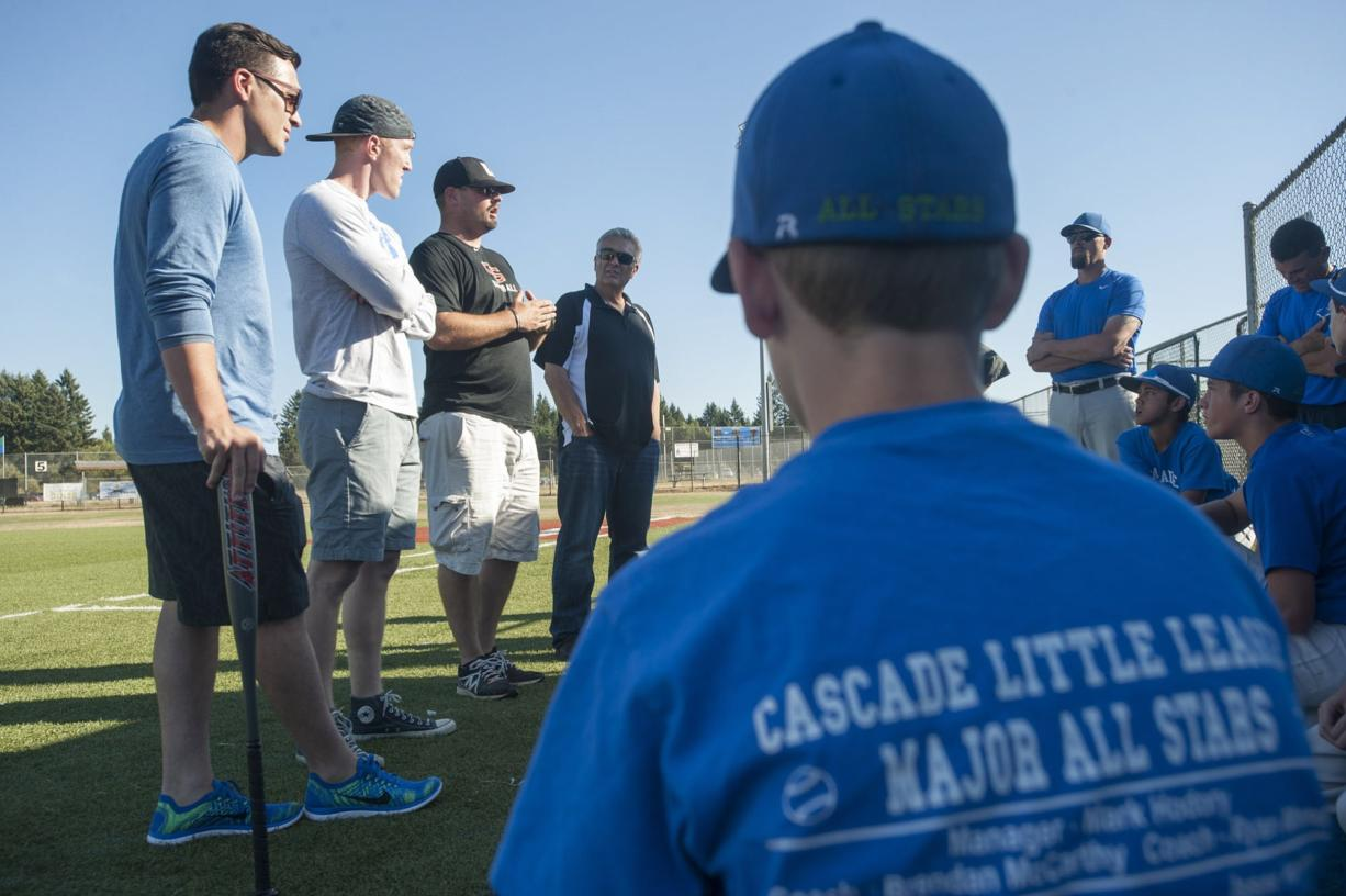 From left, former Hazel Dell Little League baseball players Jay Ponciano, Jackson Evans, Union High School coach Ben McGrew and former Hazel Dell coach Jim Ponciano give the Cascade Little League players advice prior to practice in Vancouver on Tuesday August 4, 2015.