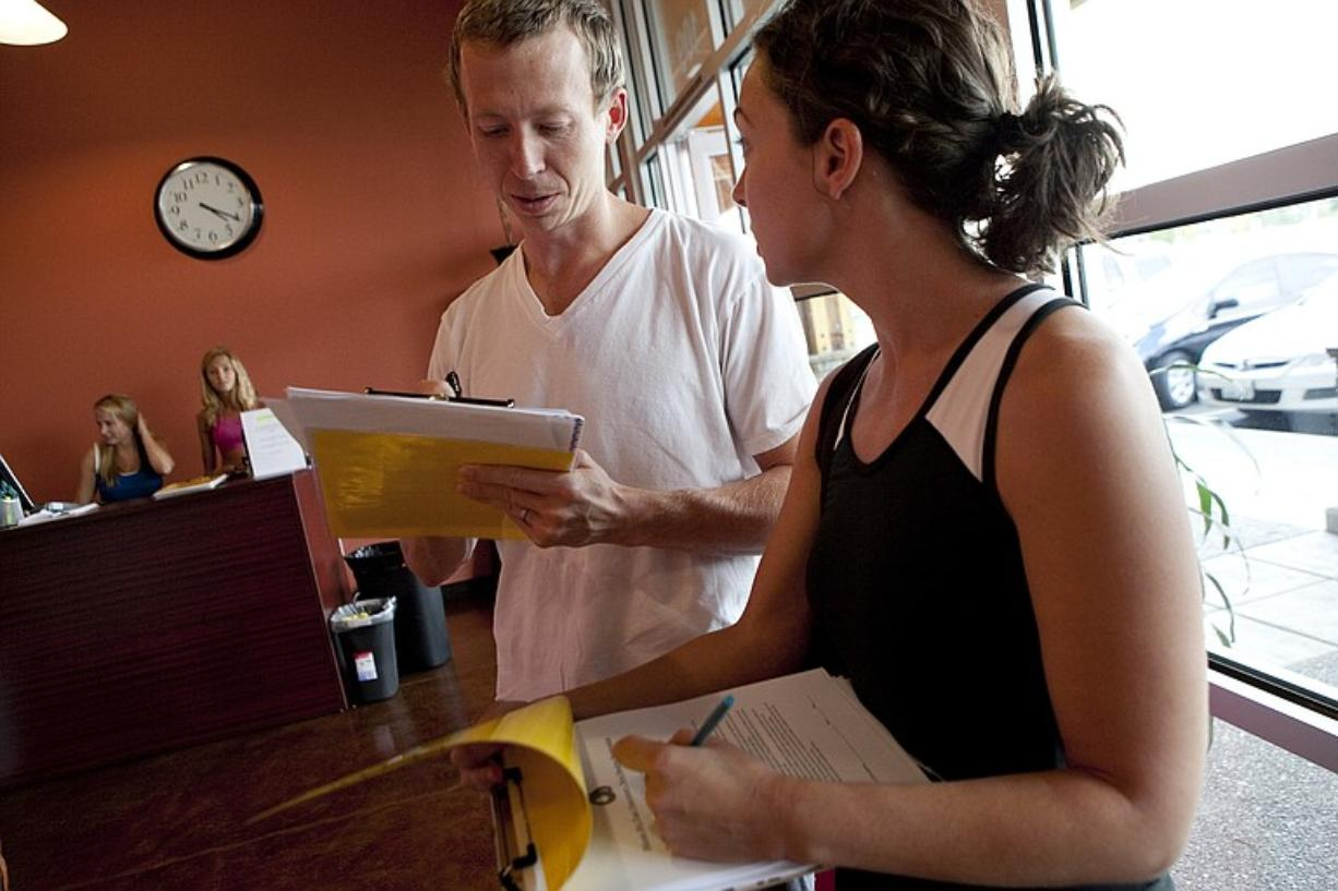 First-time Bikram Hot Yoga Vancouver students Laura Nevivs and her husband, Joe Sobolewski, sign up with a Groupon coupon they purchased online.