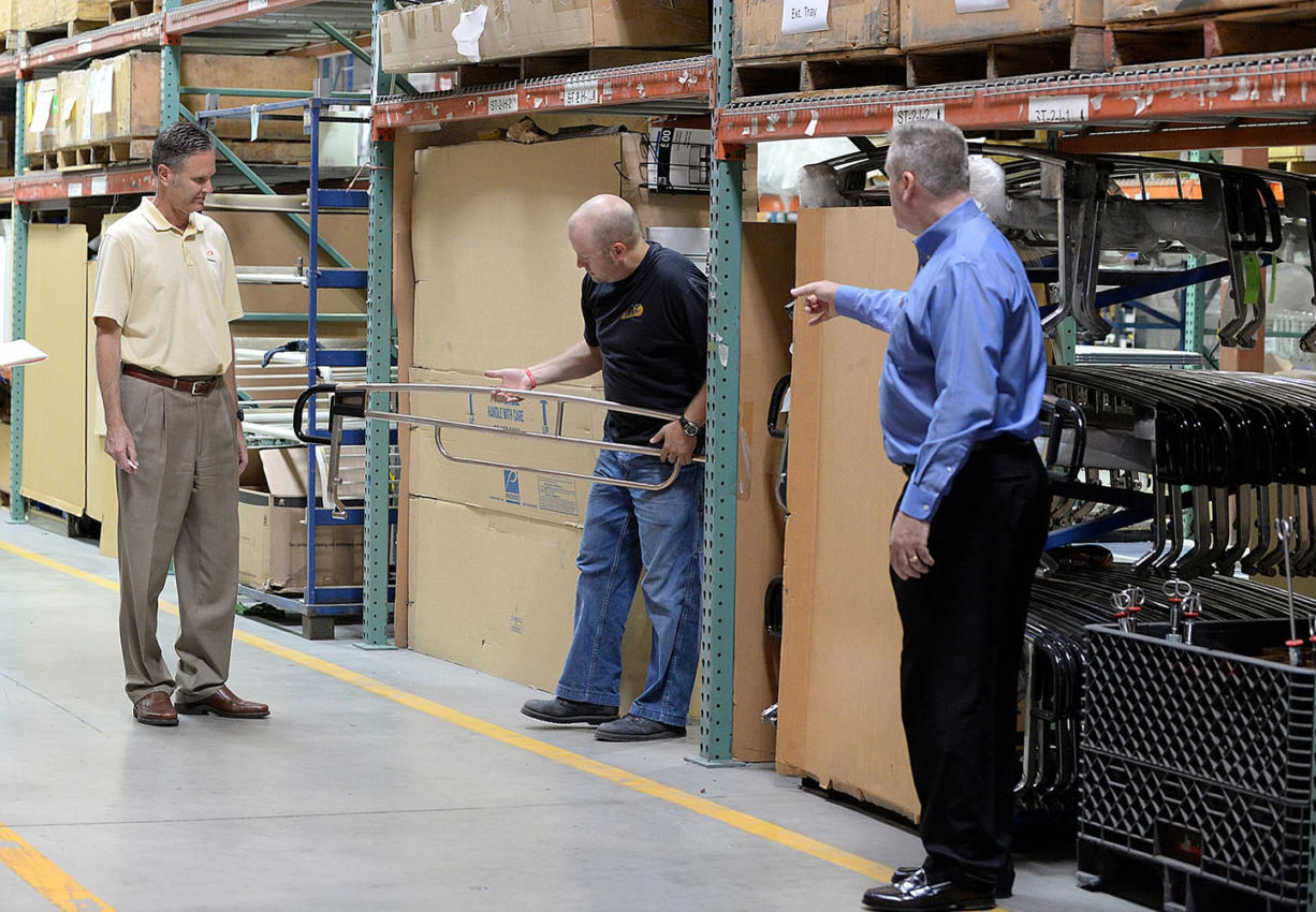 Neal Bradshaw, a manufacturing engineer at Pedigo Products, center, holds a copper handrail for a hospital stretcher as Rick Pedigo, chief executive officer, left, and Eric Hjort, director of business development, discuss the new product at the company's headquarters in Vancouver.