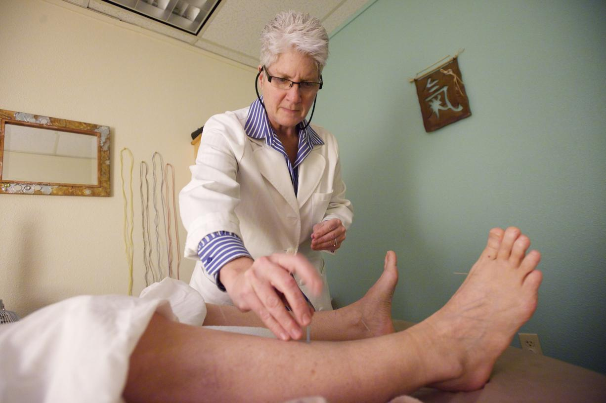 Acupuncturist Barbara Beale works with a patient Tuesday in Vancouver.
