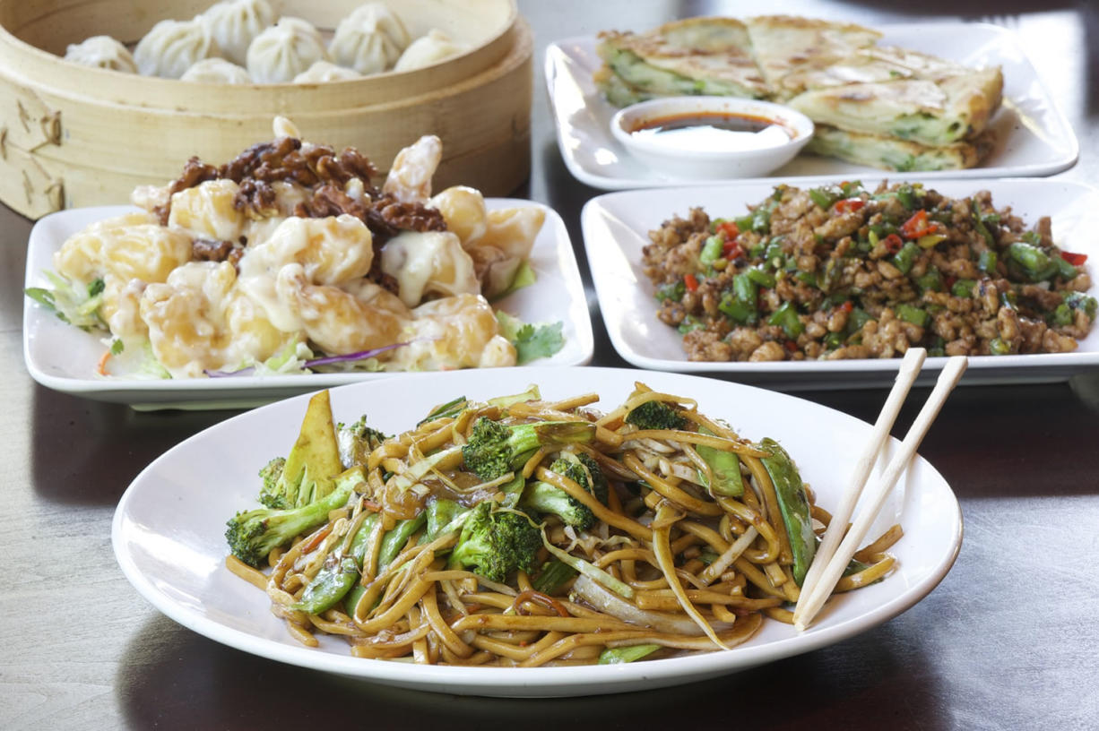 Chow mein with vegetables, crispy walnut prawns, chopped pepper hot chicken, green onion pancakes and steamed dumplings are served Oct.