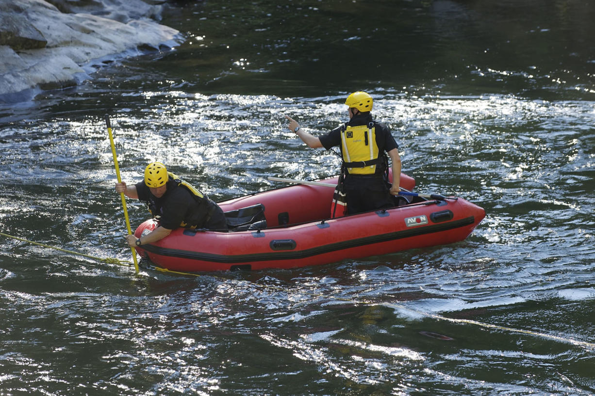 Rescue personnel from North Country EMS search the East Fork of the Lewis River below Moulton Falls on Tuesday for a man who drowned.