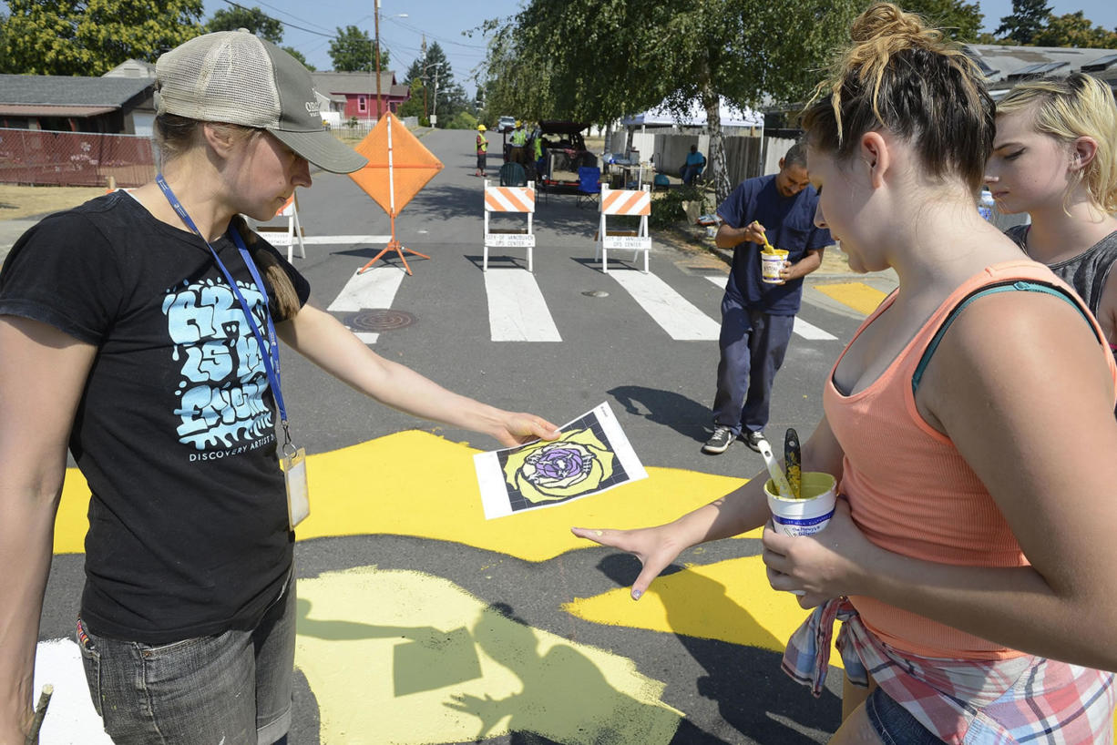 Ariane Kunze/The Columbian Discovery Middle School art teacher Miranda Wakeman (left) and Haven Rinehart, 12, review plans for a street mural at the corner of East 33rd and R streets in Rose Village. The attention-getting mural is meant to discourage drivers from speeding through the neighborhood.