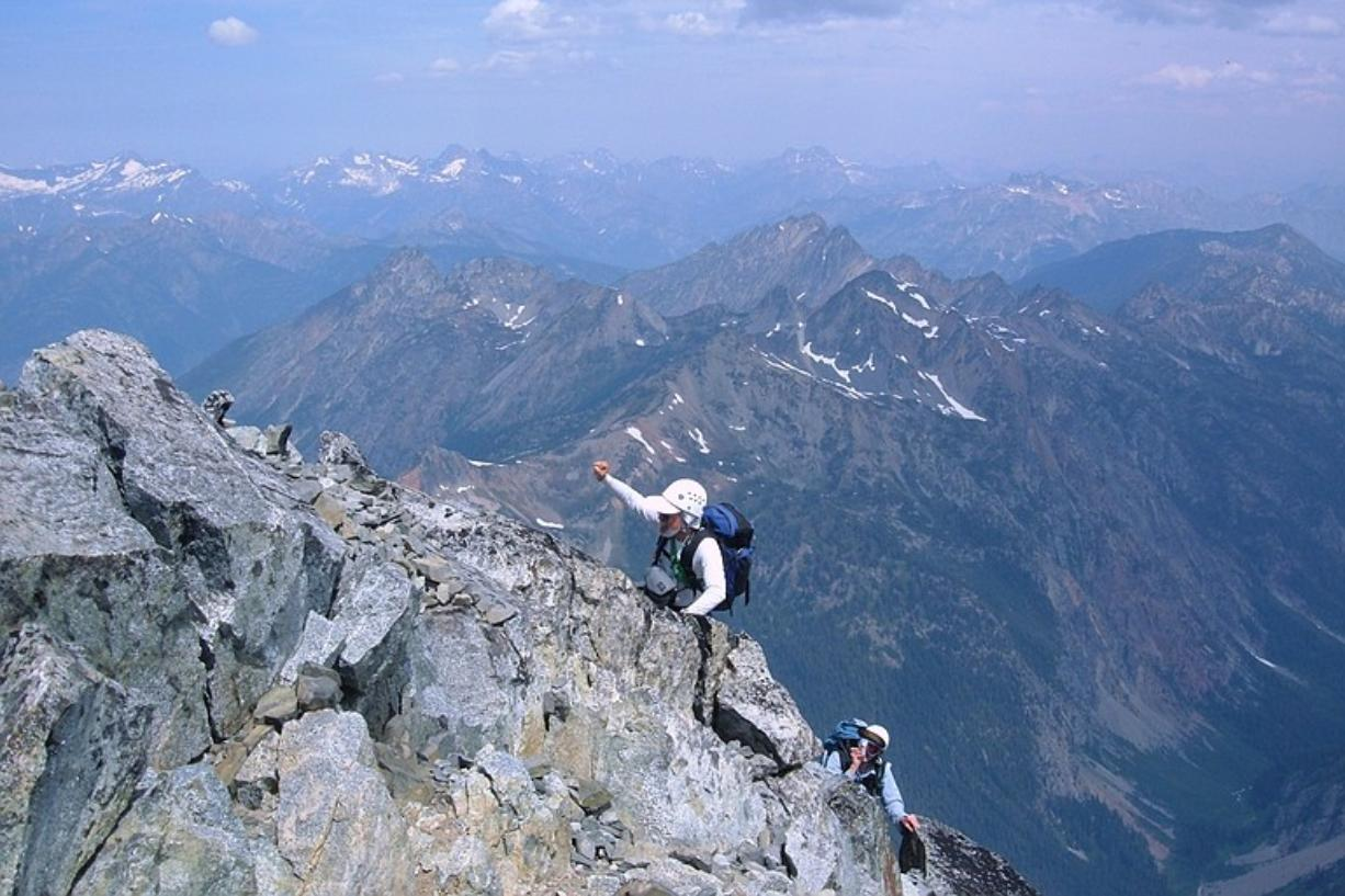 Bob Bolton raises his arms in celebration as he nears the top of Bonanza Peak, the highest point in Chelan County.
