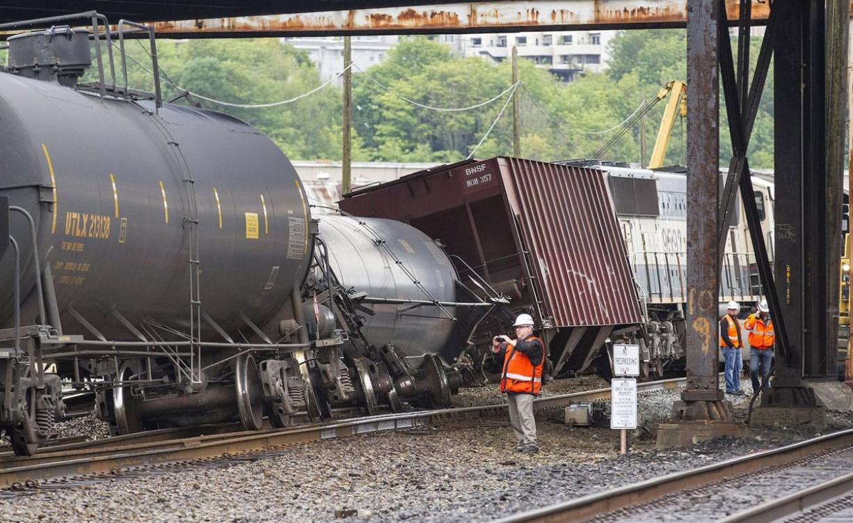 An investigator photographs the scene where a locomotive and cars carrying crude oil went off the track beneath the Magnolia Bridge in the Interbay neighborhood of Seattle on Thursday morning.