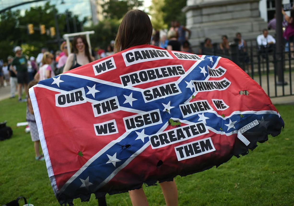 Mariangeles Borghini holds a burned Confederate flag during a rally to take down the Confederate flag at the South Carolina Statehouse on Saturday in Columbia, S.C. Rep.