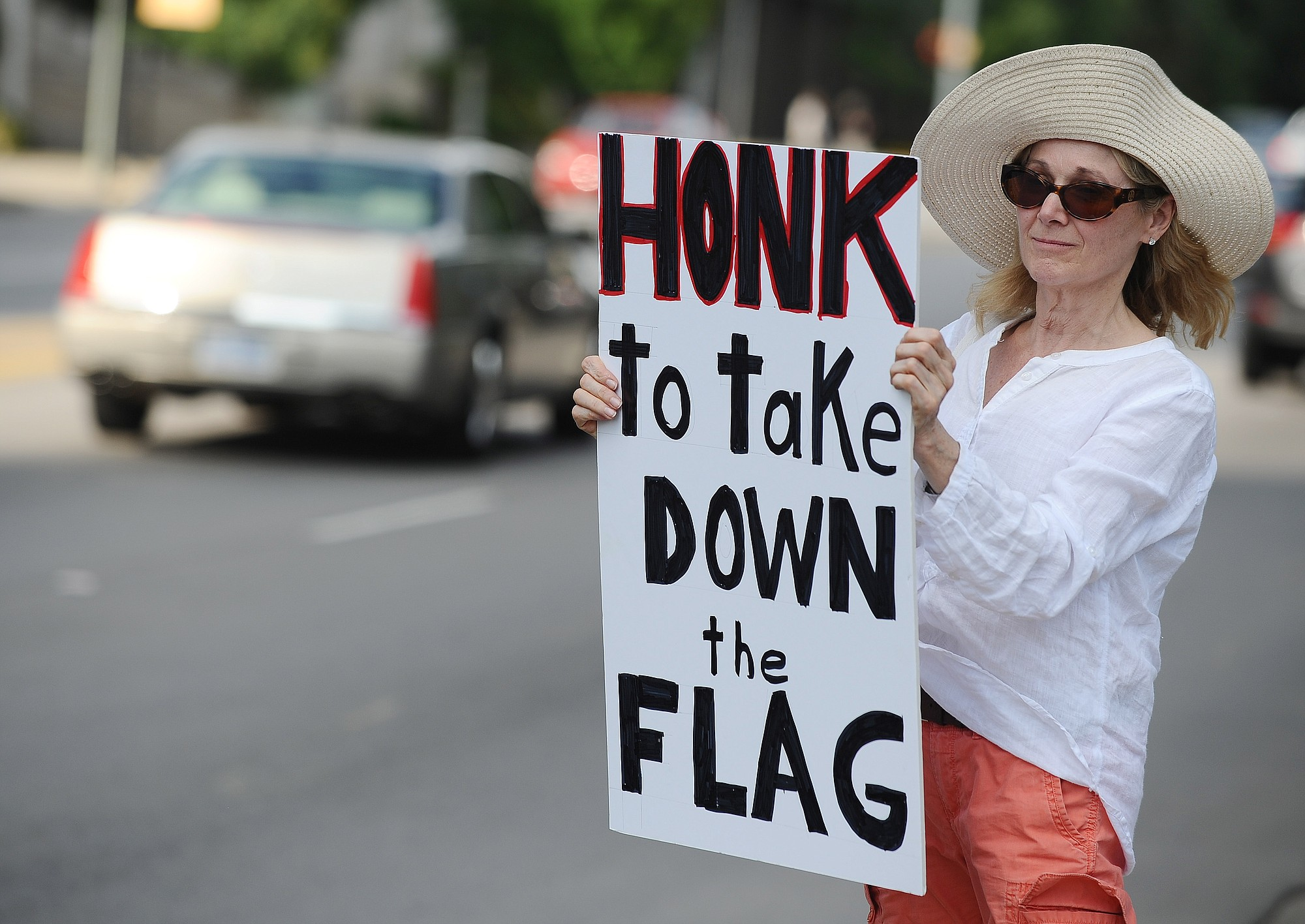 Sheila DiCioccio holds a sign during a rally to take down the Confederate flag at the South Carolina Statehouse on Saturday in Columbia, S.C. Rep. Doug Brannon, R-Landrum, said it's past time for the Confederate flag to be removed from South Carolina's Statehouse grounds after nine people were killed at the Emanuel AME Church shooting.