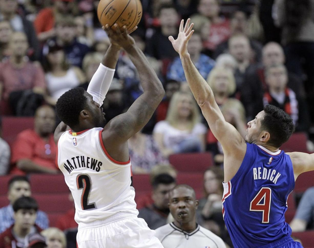 Portland Trail Blazers guard Wesley Matthews, left, shoots over Los Angeles Clippers guard J.J. Redick during the first half of Sunday's preseason game in Portland, Ore., Sunday, Oct. 12, 2014.(AP Photo/Don Ryan)