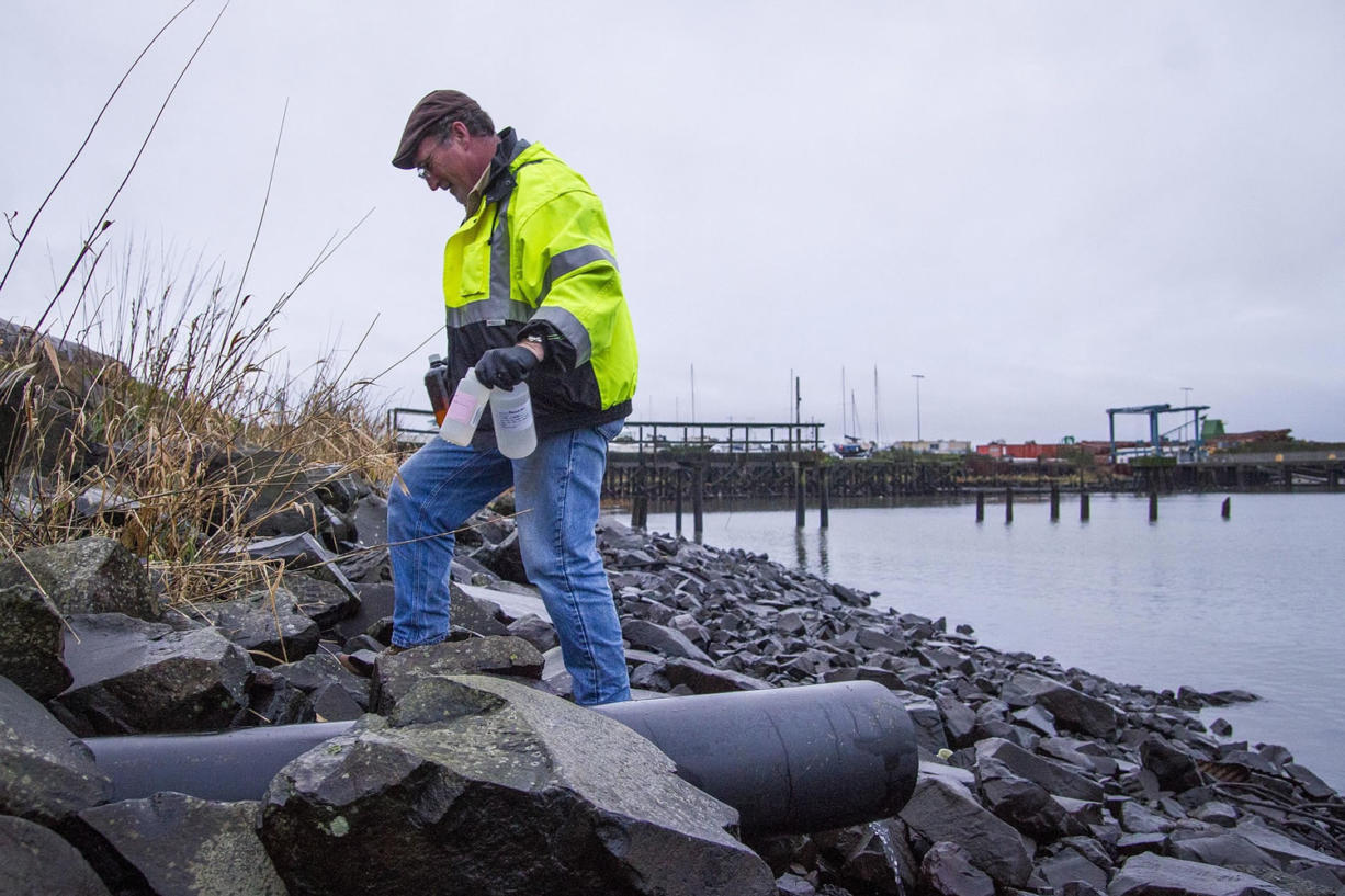Robert Evert, permit and project manager for the Port of Astoria, collects samples along Pier 2 in Astoria, Ore. Federal regulators said Friday that Oregon logging rules do not sufficiently protect water and fish from pollution.