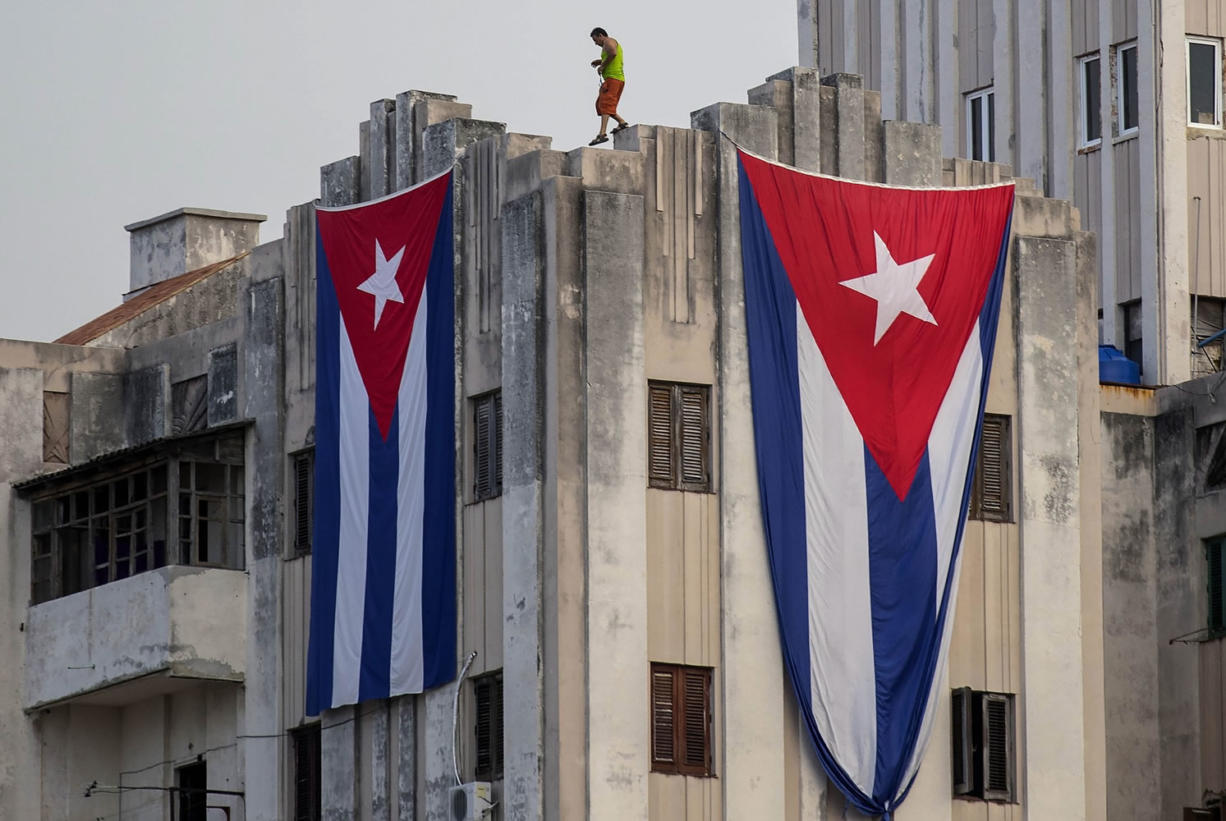 A man walks along the ledge of a building after hanging two giant Cuban flags, next to the U.S. embassy in Havana, Cuba, on Tuesday.