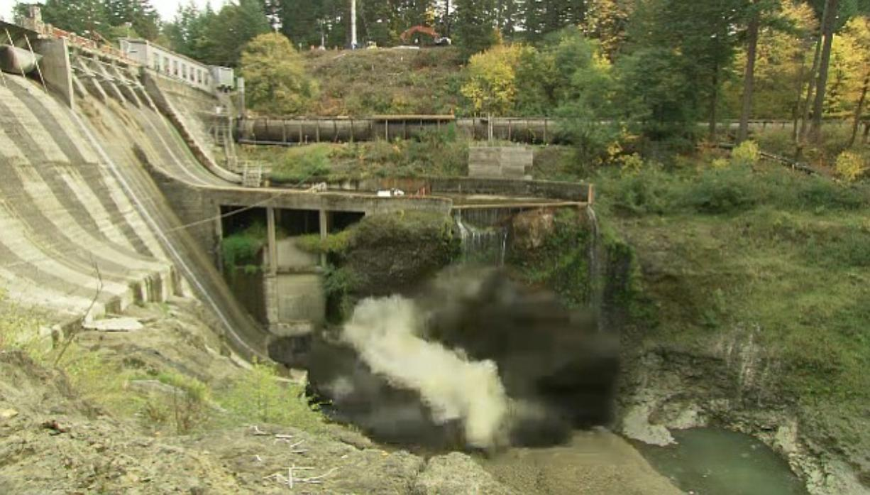 The first dust and smoke emerges from the base of Condit Dam as a 700-pound charge of TNT detonates, clearing the final section of tunnel underneath the dam.