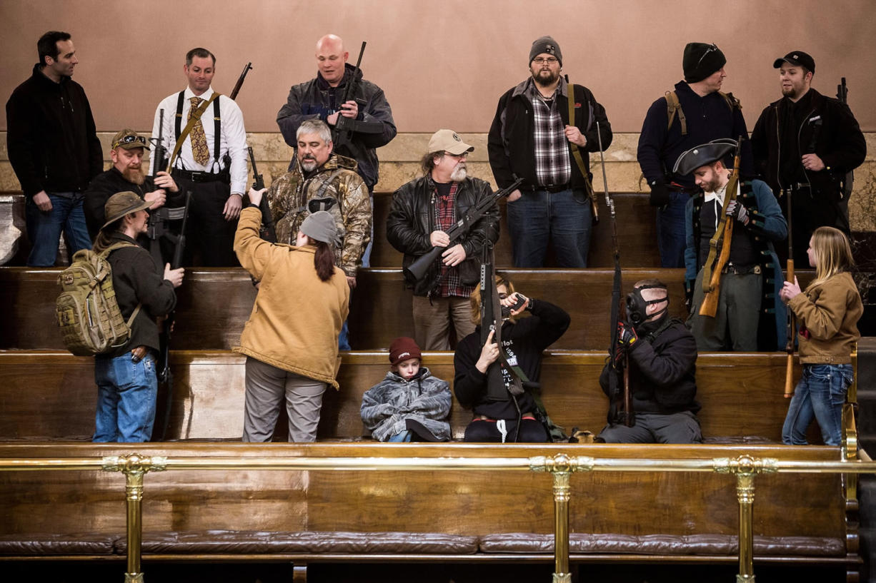 Demonstrators with weapons file into the pews of the House Gallery on Thursday to demand support to reverse Initiative 594 during a rally in the Capitol building in Olympia. The lieutenant governor announced Friday that open carry of guns has been banned in the Senate's public viewing area. No decision has been made on openly carrying guns in the House's public gallery. (AP Photo/seattlepi.com, Jordan Stead)
