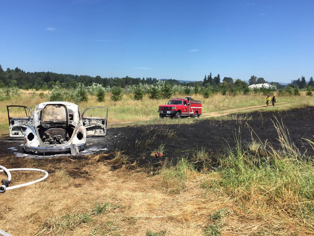 Remains of a burned-out Volkswagen Beetle sit in a field after a car fire spread to dry grass off Northeast 259th Street on Thursday.