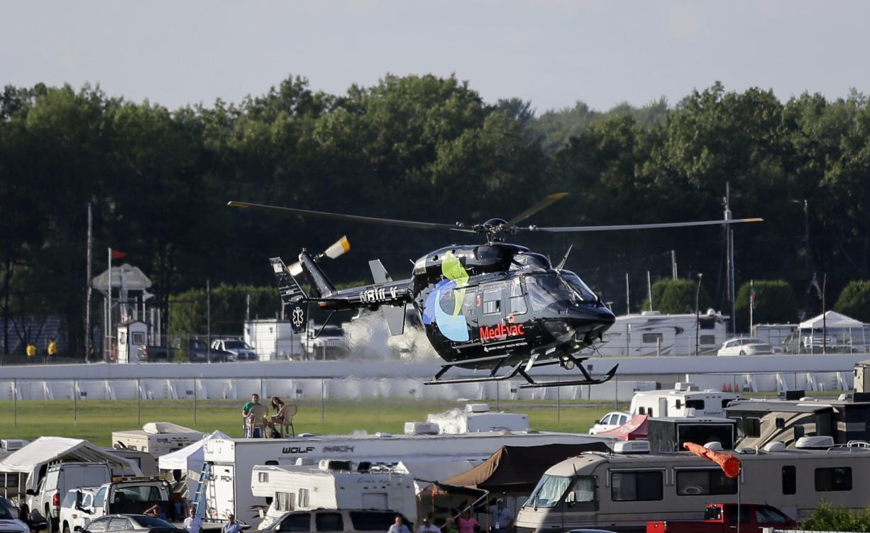 A helicopter lifts off at Pocono Raceway carrying race car driver Justin Wilson, of England, after he was involved in a crash during the Pocono IndyCar 500 auto race Sunday, Aug. 23, 2015, in Long Pond, Pa.