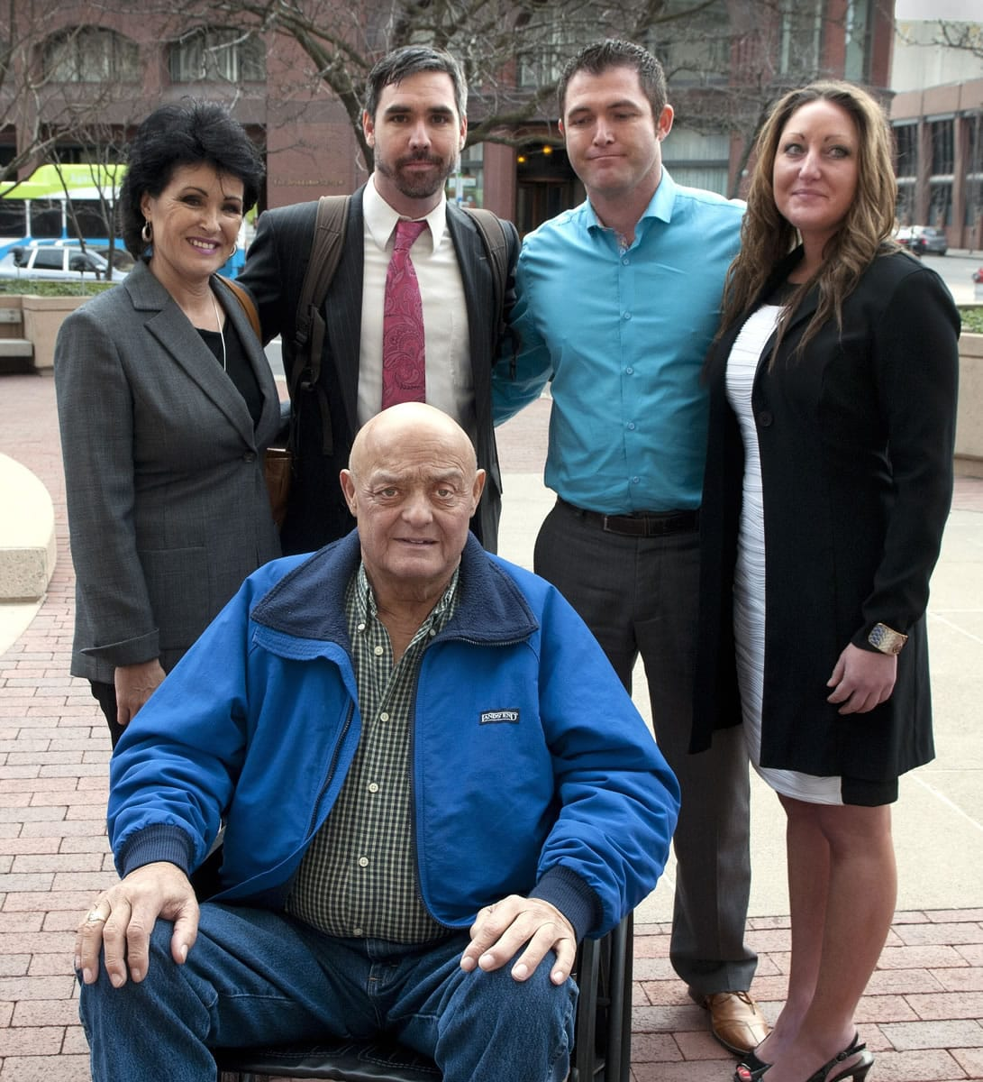 Larry Harvey is seated in front of, from left, Rhonda Lee Firestack-Harvey, Jason Zucker, Rolland Gregg and Michelle Gregg outside the Thomas S. Foley United States Courthouse in Spokane.