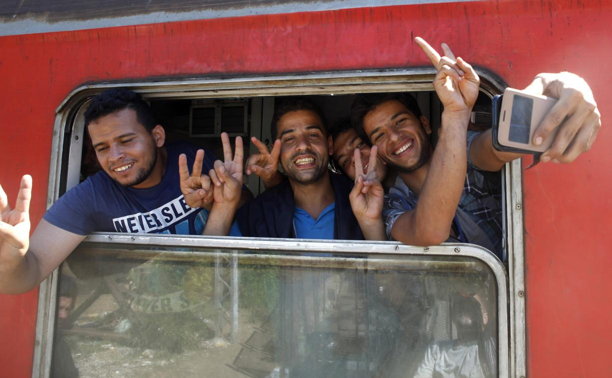 Migrants from Syria take a selfie and flash victory signs from a window of a train that would take them towards Serbia, at the railway station in the southern Macedonian town of Gevgelija, on Monday.