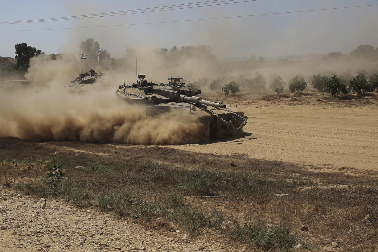 An Israeli tank advances to a staging area near the Israel-Gaza border on Tuesday.