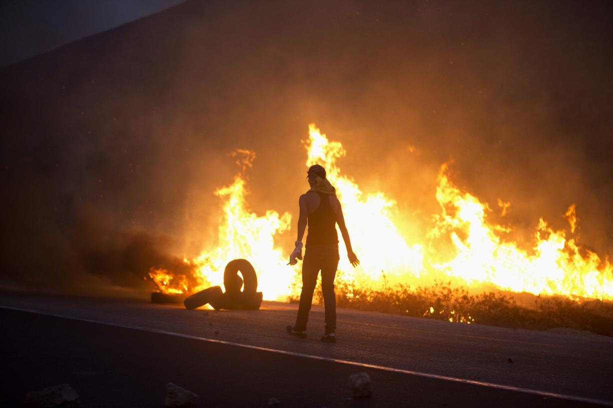 A Palestinian demonstrator burns tires in clashes with Israeli soldiers Sunday near the West Bank city of Nablus.