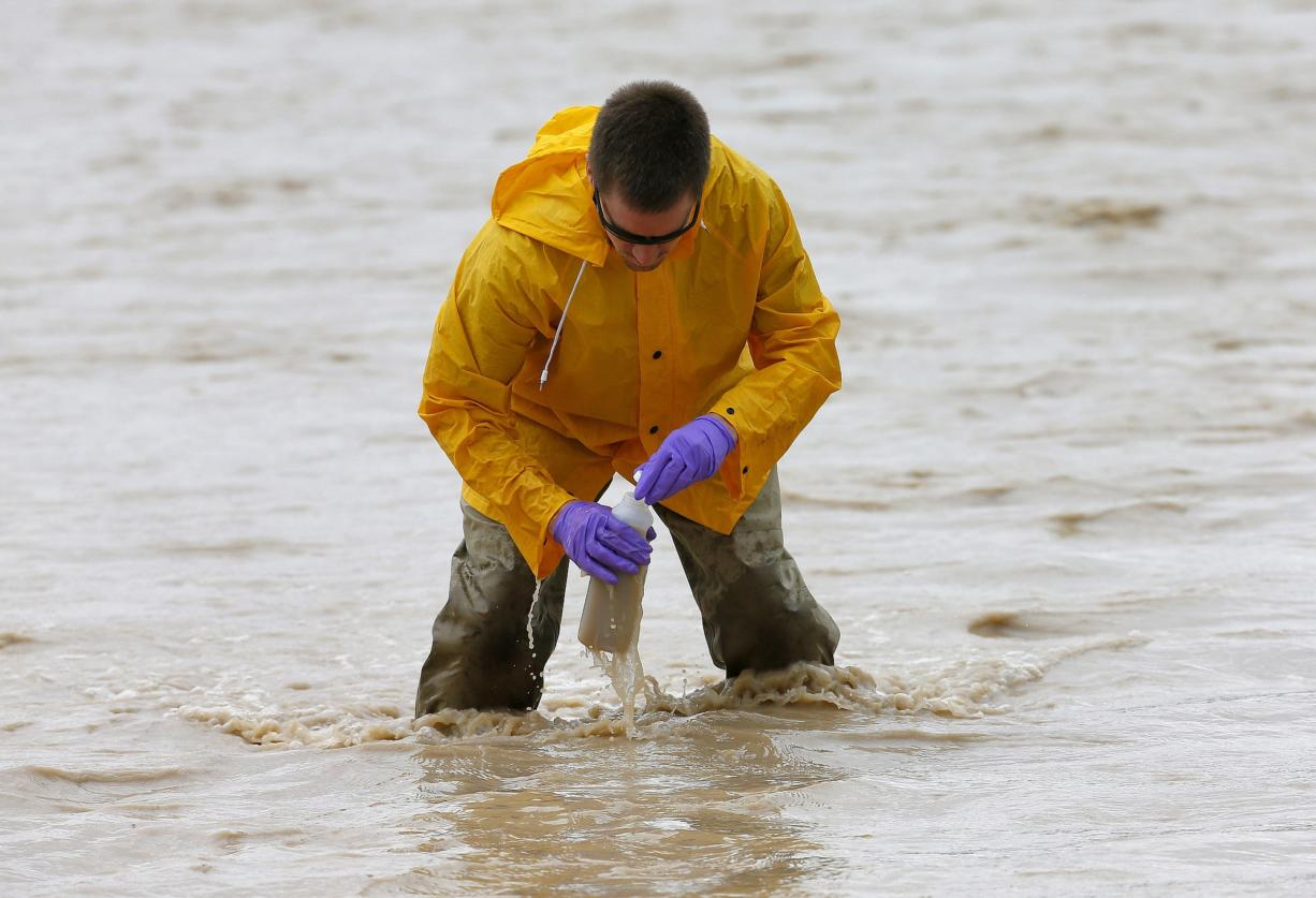 Hydrologic Technician Ryan Parker gathers water samples from the San Juan River, Tuesday, Aug. 11, 2015, in Montezuma Creek, Utah. A spill containing lead and arsenic from the abandoned Gold King Mine in Silverton, Colo., leaked into the Animas River, which flows into the San Juan River in southern Utah, on Aug. 5. The spill was caused by a mining and safety team working for the EPA.