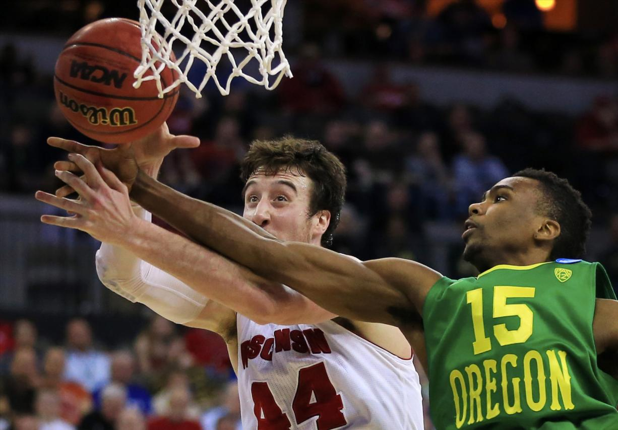 Oregon's Jalil Abdul-Bassit (15) and Wisconsin's Frank Kaminsky (44) compete for a rebound during the second half of an NCAA tournament game in Omaha, Neb., Sunday, March 22, 2015.