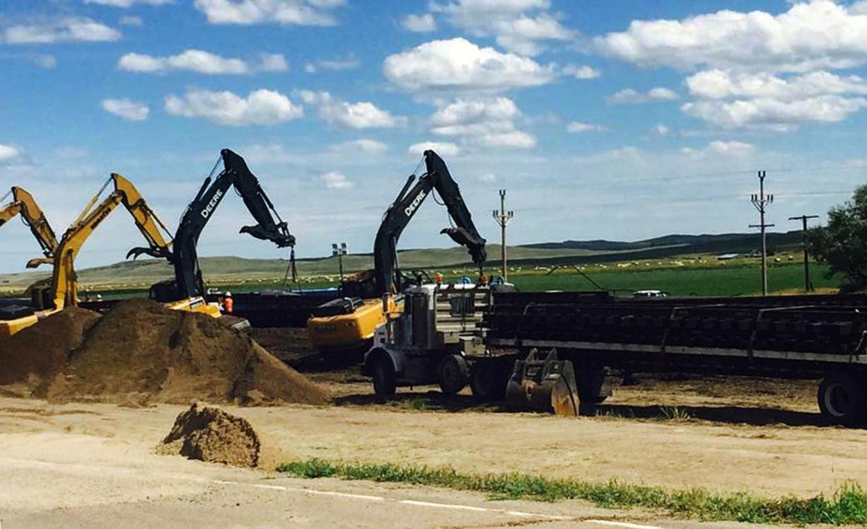 Crews with cranes attempt to raise derailed oil tanker cars near Culbertson, Mont., Friday, July 17, 2015. The tank cars were hauling fuel from North Dakota and derailed Thursday in rural northeastern Montana, authorities said. (AP Photo/Richard Peterson)