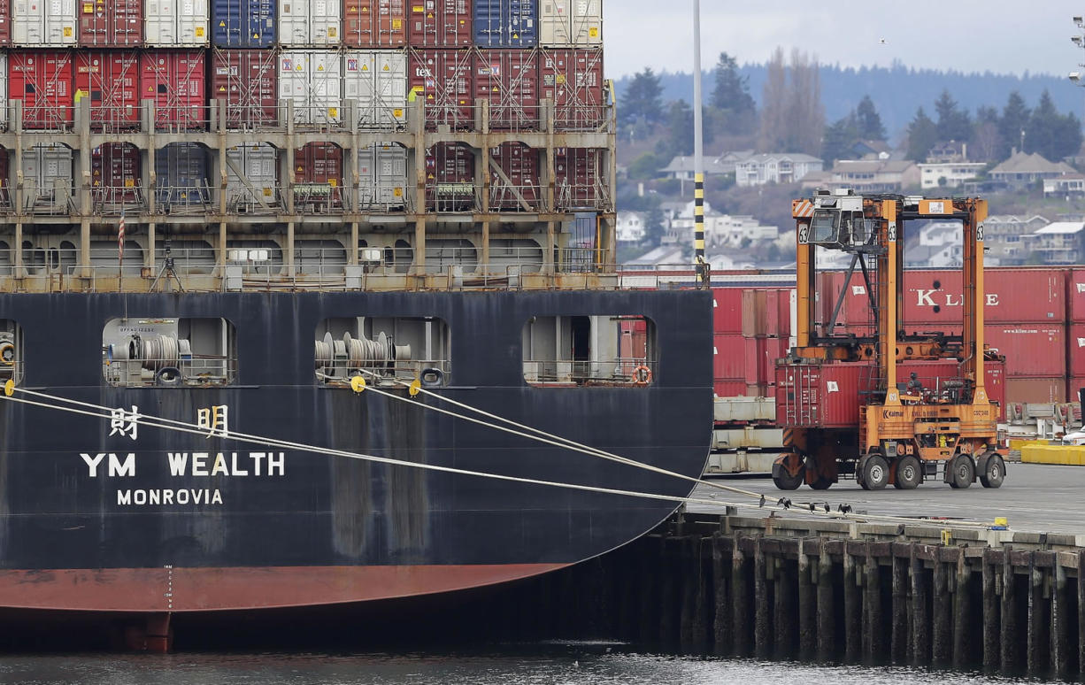 A cargo container mover carries a container at right next to a cargo ship operated by Yang Ming Marine Transport Corp. at the Port of Tacoma, Friday in Tacoma.
