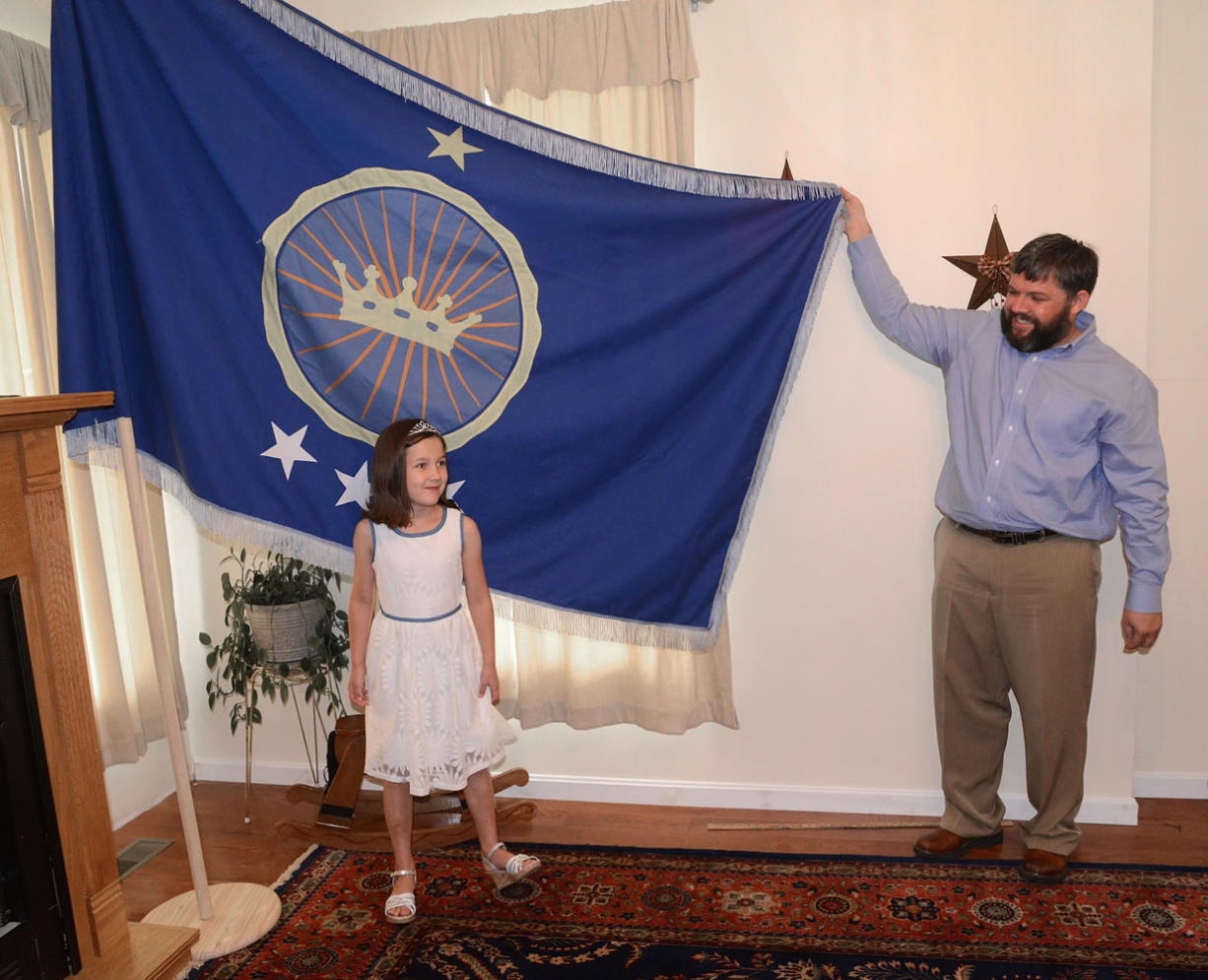 Jeremiah Heaton and his seven year-old daughter, Princess Emily, show the flag,July 2, 2014, in Abingdon, Va,  that their family designed as they try to claim a piece of land in the Eastern African region of Bir Tawil. (AP Photo/Bristol Herald Courier, David Crigger)