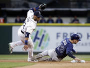 Seattle Mariners second baseman Robinson Cano, left, is tripped by the feet of Tampa Bay Rays' Steven Souza Jr.