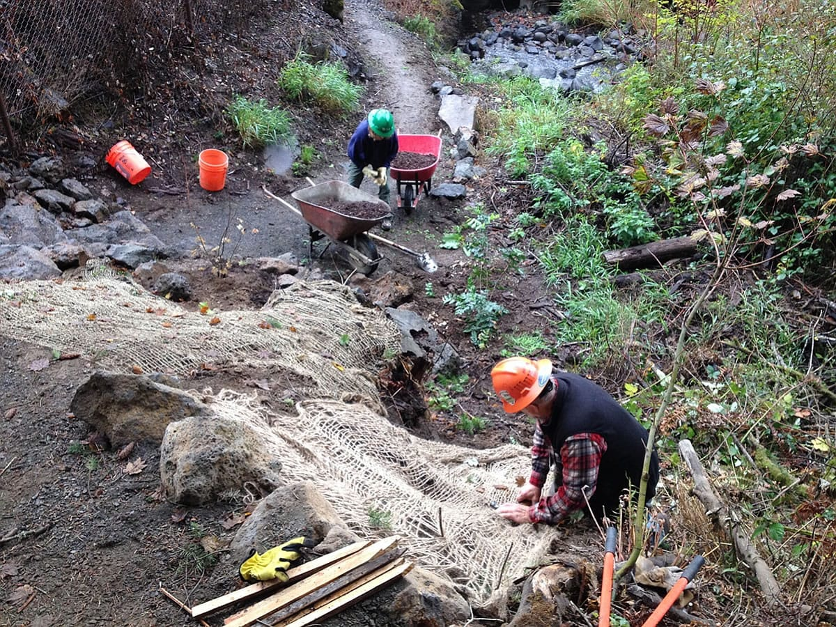 Ryan Ojerio/Washington Trails Association      Washington Trails Association volunteers build up the slope for the River to Rock Trail, a new connector path that links the day-use area to the trail to the top of Beacon Rock State Park.