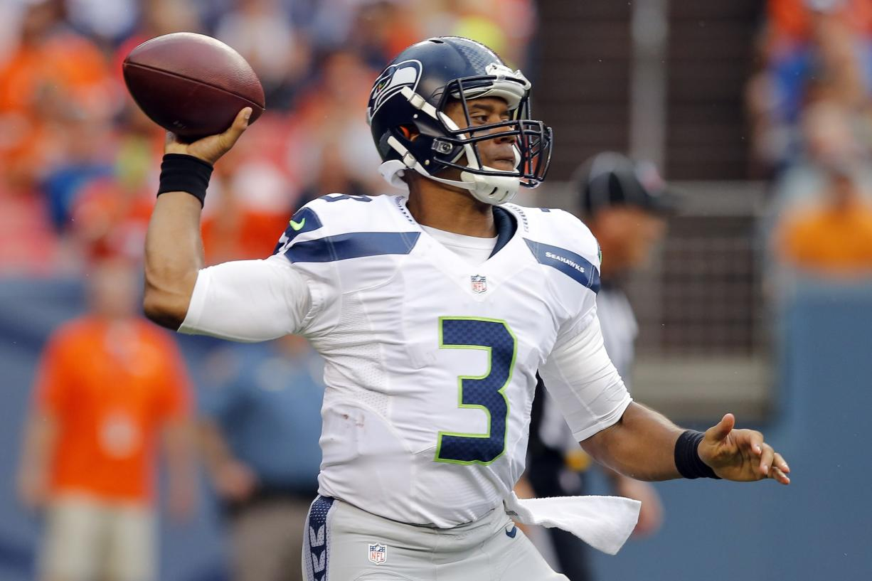 Seattle Seahawks quarterback Russell Wilson (3) throws against the Denver Broncos during the first half of an NFL preseason football game, Thursday, Aug. 7, 2014, in Denver. (AP Photo/Jack Dempsey)