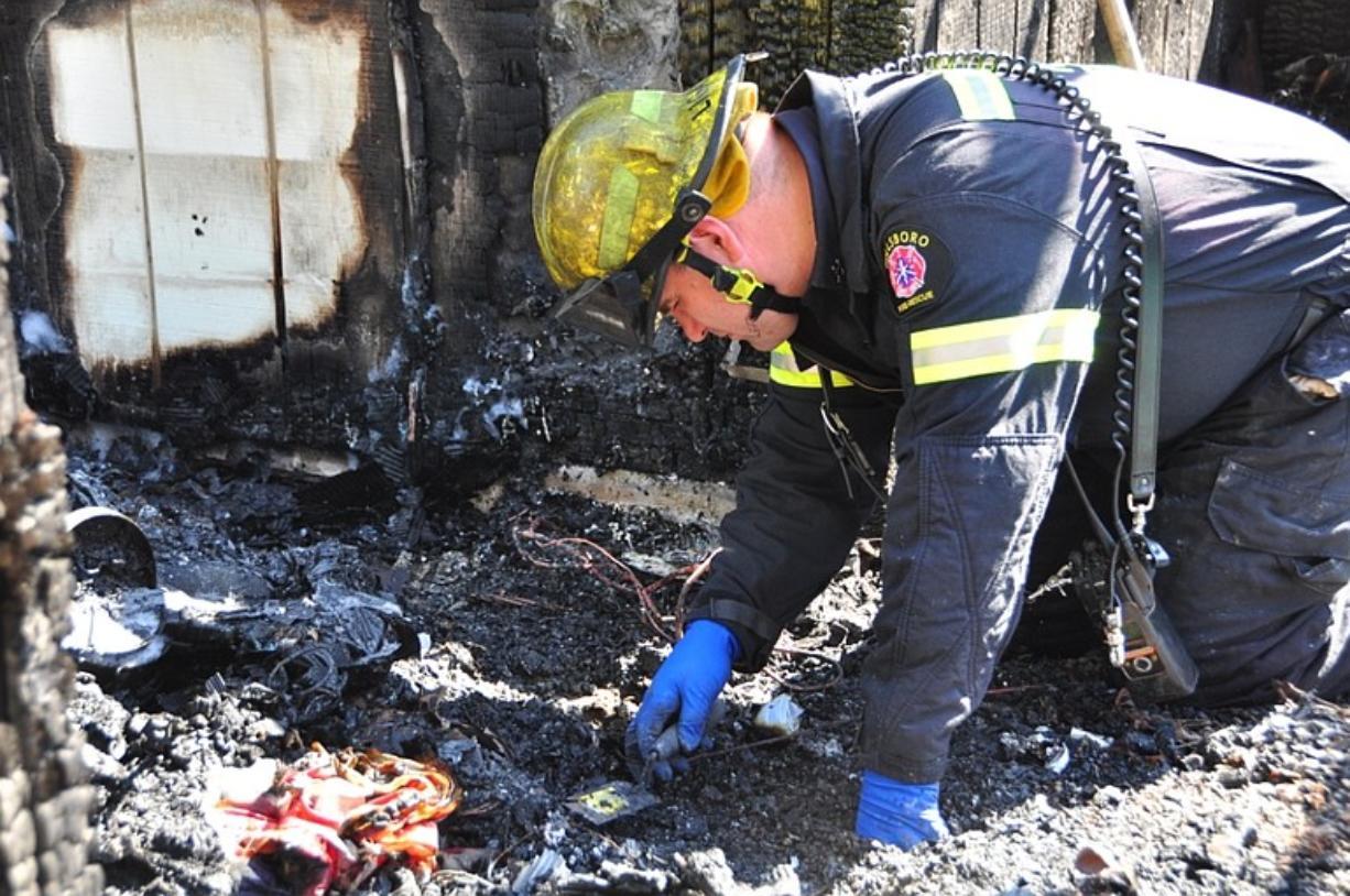 A fire investigator looks through the ruins of a Hillsboro, Ore.