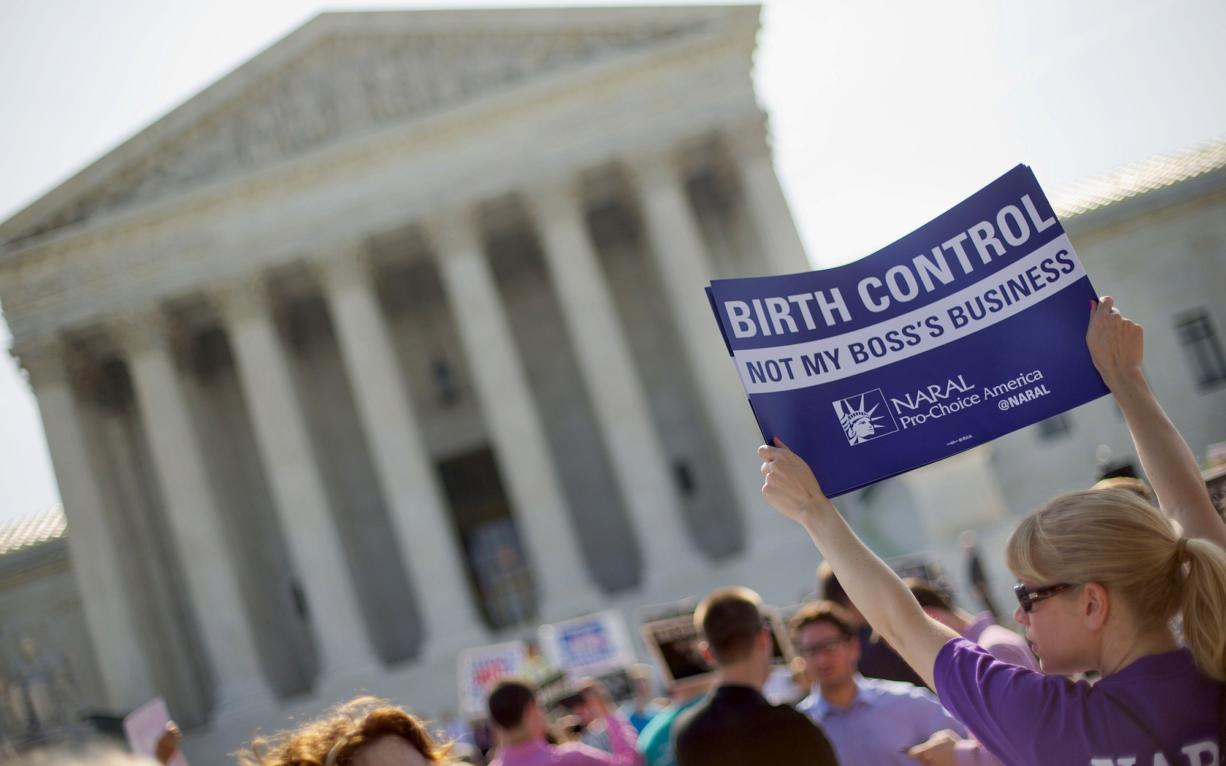 A demonstrator holds up a sign June 30 outside the Supreme Court in Washington on the day the court decided in the Hobby Lobby case to relieve businesses with religious objections of their obligation to pay for women's contraceptives among a range of preventive services the new health law calls for in their health plans.