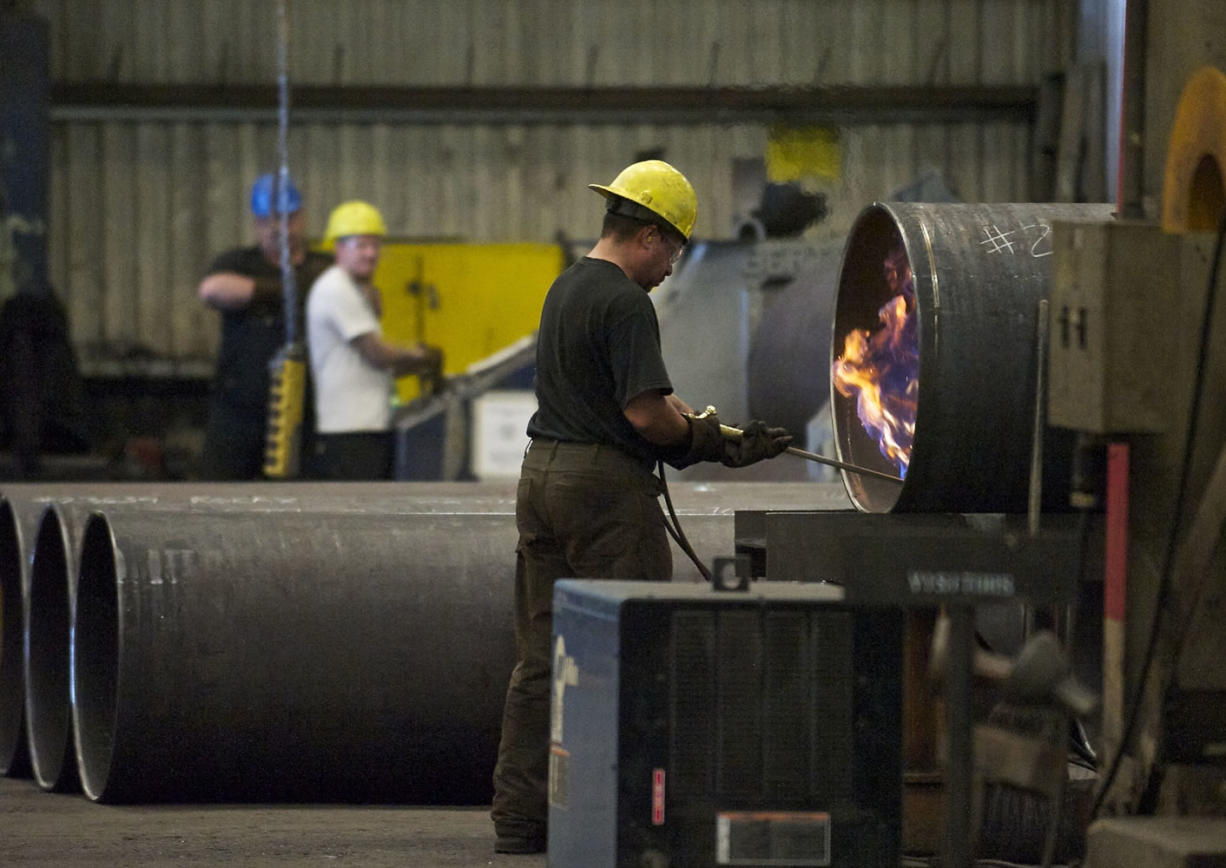 An employee fires up a torch inside the Thompson Metal Fab facility during a tour in July 2013.