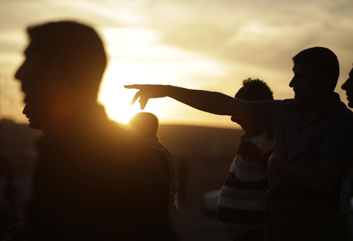 Turkish Kurds watch as airstrikes hit Kobani, inside Syria, as fighting intensifies between Syrian Kurds and the militants of Islamic State group, in Mursitpinar, on the outskirts of Suruc, at the Turkey-Syria border Wednesday.