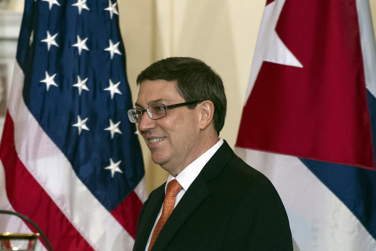 Cuban Foreign Minister Bruno Rodriguez walks past American and Cuban flags as he joins Secretary of State John Kerry at a news conference Monday in Washington.
