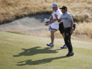 Jason Day walks up to the 18th green with his caddie Colin Swatton during third round of the U.S. Open at Chambers Bay on Saturda in University Place. Day is tied for the lead at 4-under par despite suffering from vertigo during the past two rounds.