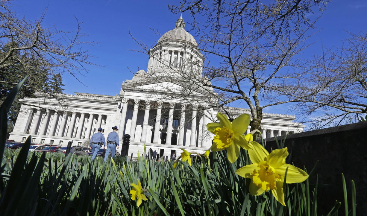 Early daffodils bloom as two Washington State Patrol troopers walk toward the Capitol, Tuesday, Feb. 17, 2015, in Olympia, Wash. Temperatures hit record highs Monday in parts of Washington and Oregon as one of the mildest winters continues in the Northwest (AP Photo/Ted S. Warren)